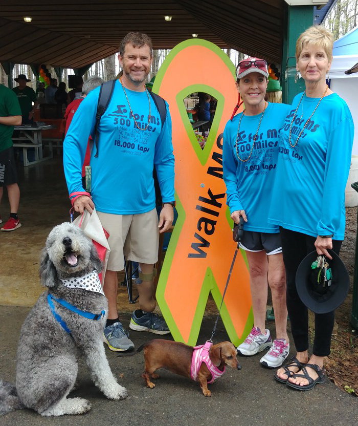 3 people with 2 dogs standing next to a ribbon for MS