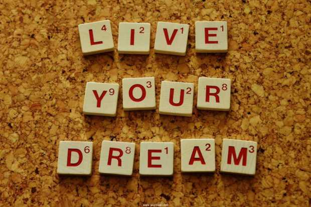 Live your dream spelled out in scrabble tiles on a cork board background
