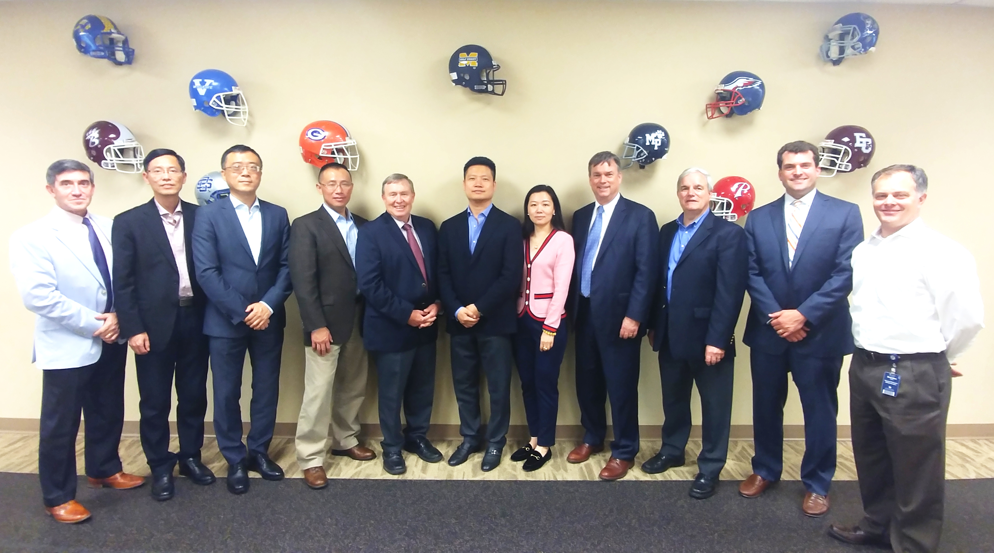 Group of people posing for picture in front of a wall with football helmets mounted on the wall in the background