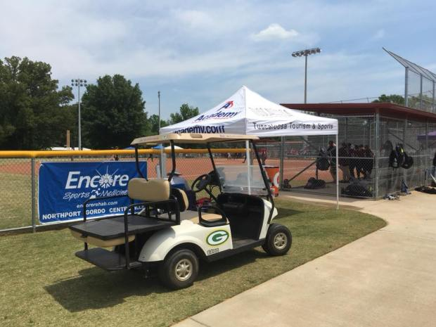 Golf cart next to softball field and dugout with Encore Sports Medicine Banner in the background during a bright spring day