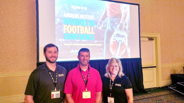 Three people from Encore Rehabilitation, Inc. pose for photo in front of movie screen displaying Andrews Institute Injuries in Football Conference