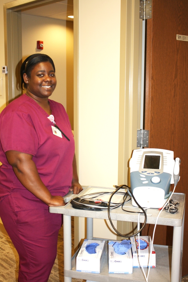 Young lady in mulberry scrubs smiling, posing with a cart holding rehab equipment