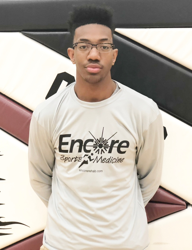 Young male athlete standing in gym with shirt that reads Encore Sports Medicine, encorerehab.com