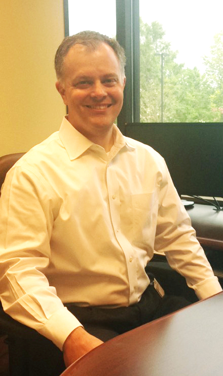 Male Physical Therapist in white long-sleeve dress shirt sitting at a desk smiling