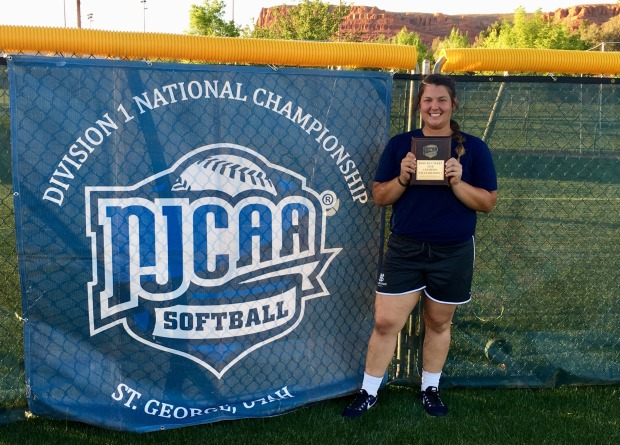Charlee West, Softball Home Run Derby Champion posing with award/plague standing in front of a banner which reads NJCAA Softball Division 1 National Championship, St. George, Utah