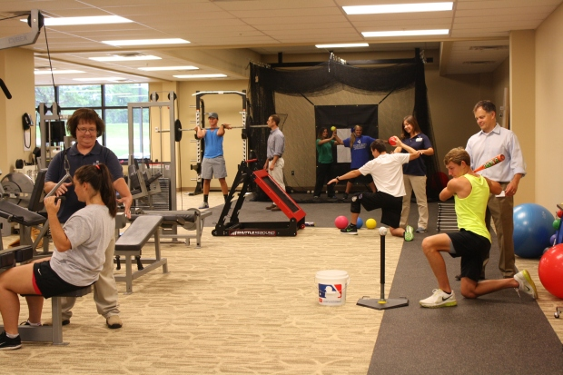 Physical Therapists and Staff working with patients and athletes in the gym area of East Lake Physical Therapy