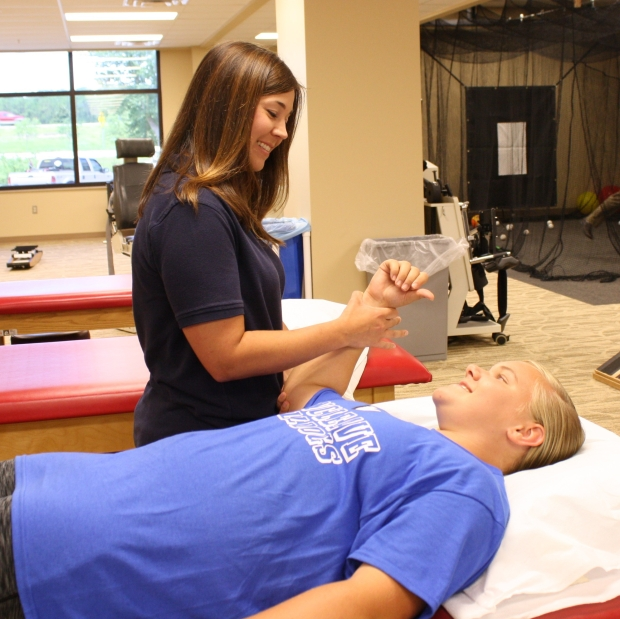 Female Physical Therapist performing shoulder exercises with young lady lying on rehab treatment table