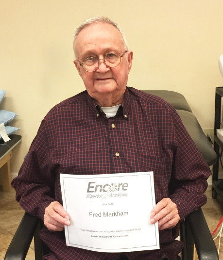 Older gentleman sitting in a chair holding a certificate that reads Fred Markham Patient of the Month for Encore Rehabilitation-Vernon