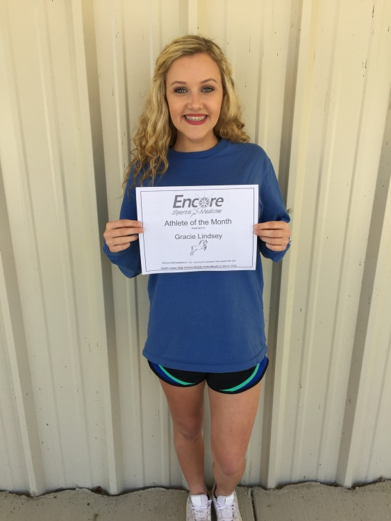 Young lady smiling and posing with a certificate declaring her Athlete of the Month for Encore Rehabilitation and Sports Medicine