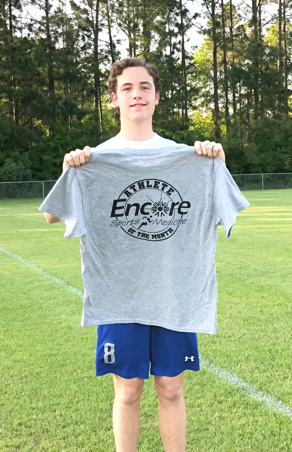 Teenaged boy dressed in t-shirt and shorts standing on a soccer field holding up a t-shirt which reads Encore Sports Medicine Athlete of the Month