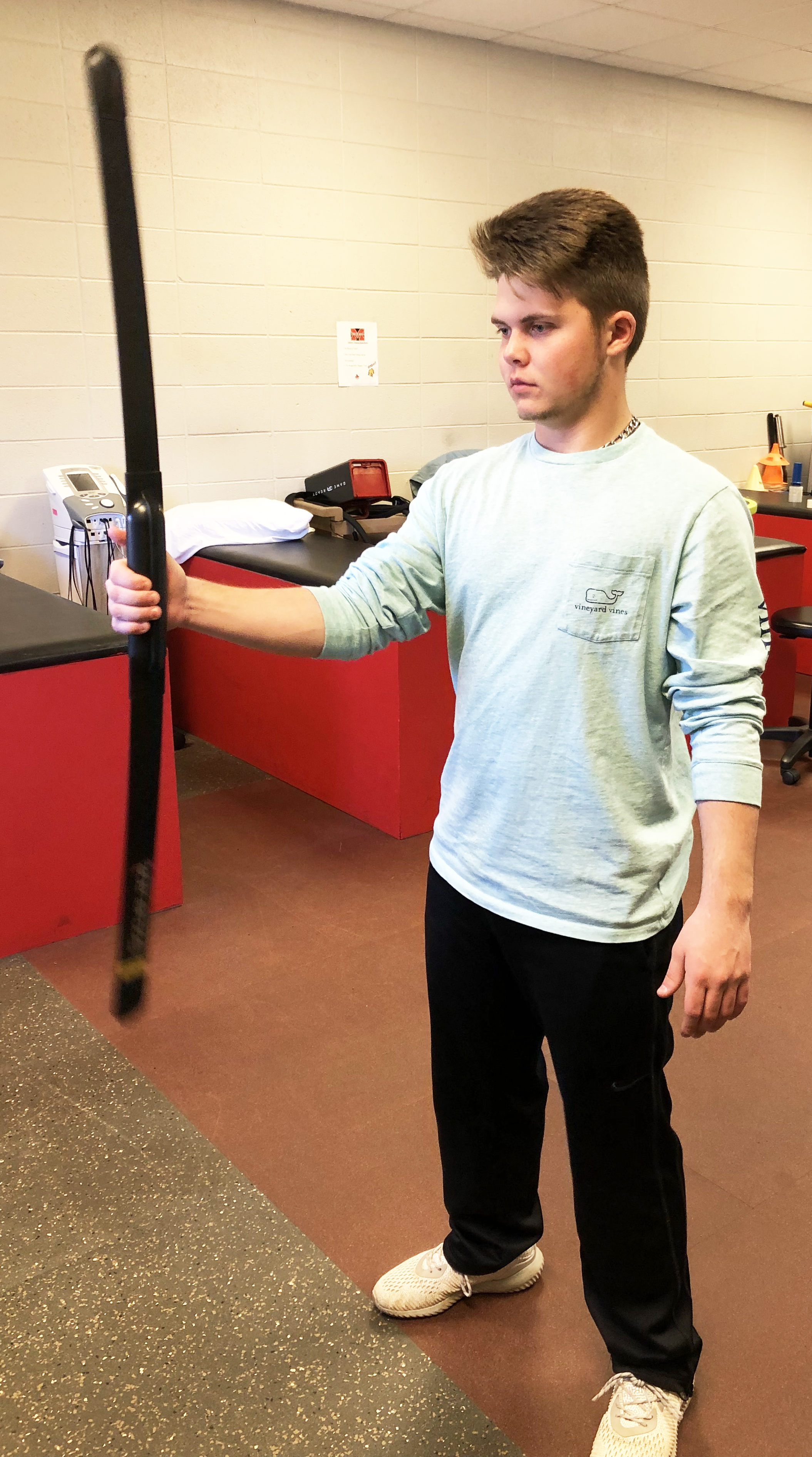 Young man holding a resistance blade exercise bar out from body