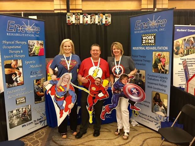 Encore Rehabilitation booth with employees with super heroes t-shirts depicting superman, the flash, and captain america.