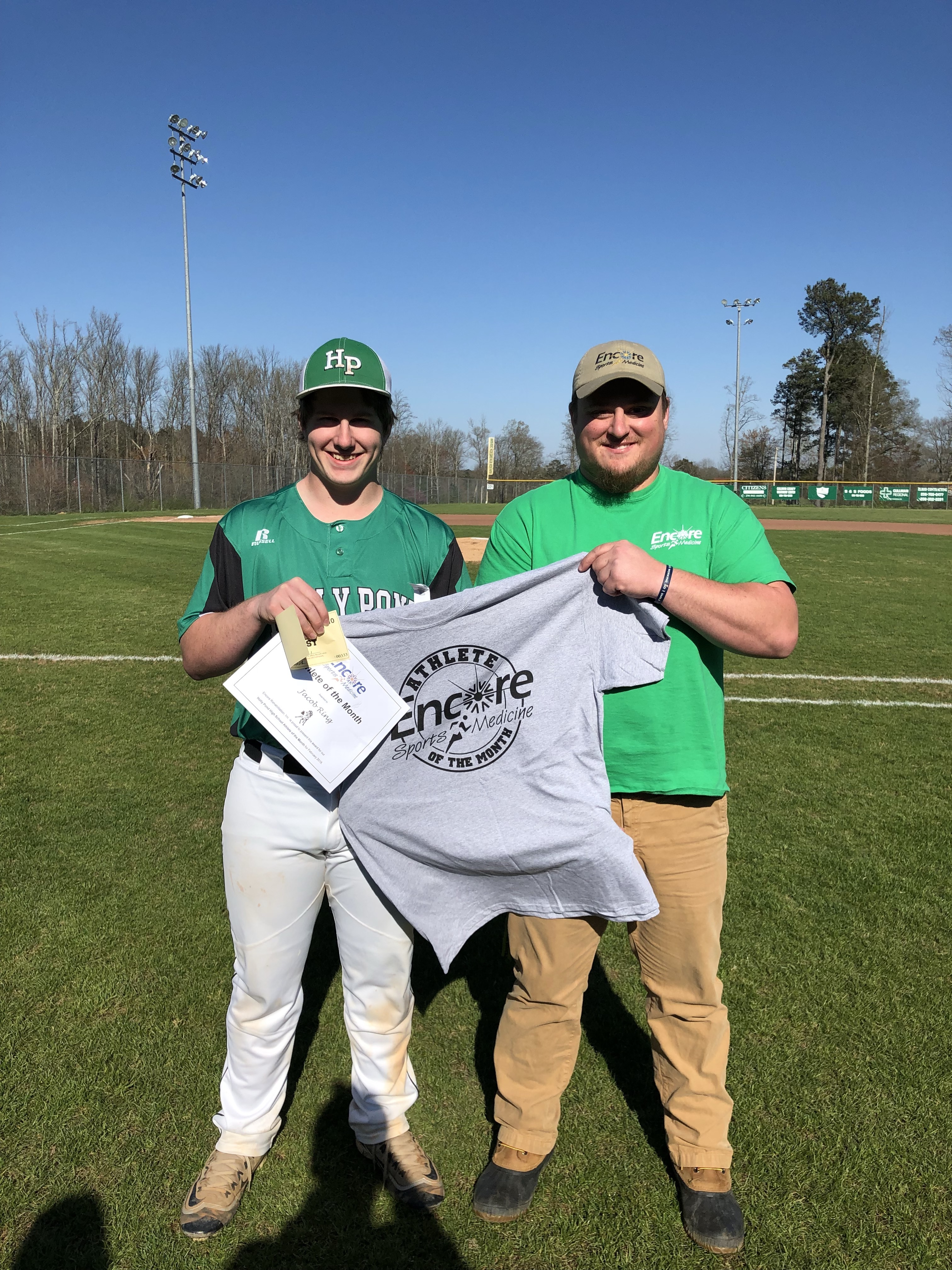 Male baseball player in uniform standing on baseball field holding a certificate and t-shirt which reads Encore Sports Medicine Athlete of the Month while male athletic trainer also helps hold shirt