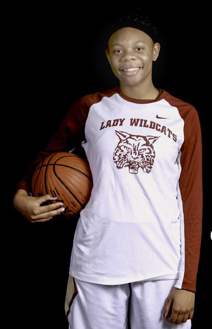Young female athlete in basketball warmup suit holding basketball on arm with Lady Wildcats on jersey