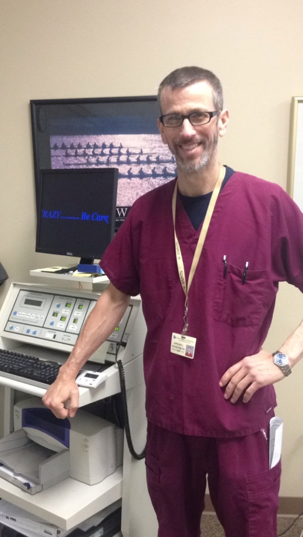Man with glasses wearing mulberry scrubs smiling while standing next to diagnostic rehab equipment