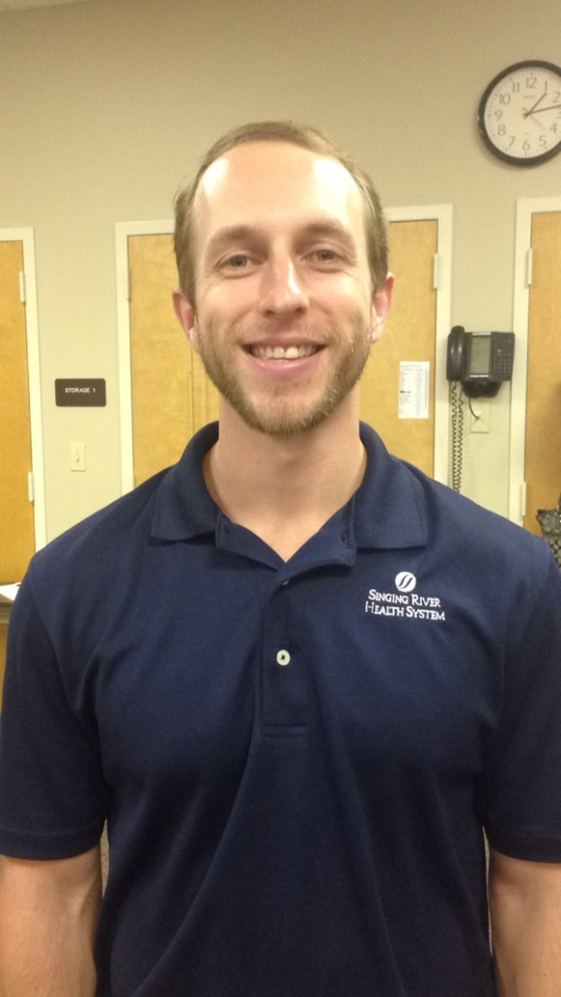 Bearded young male Physical Therapist in navy polo shirt smiling