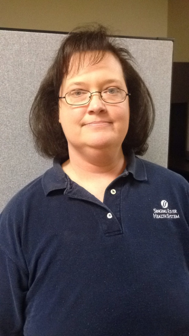 Female Physical Therapist Assistant with glasses and navy polo shirt smiling