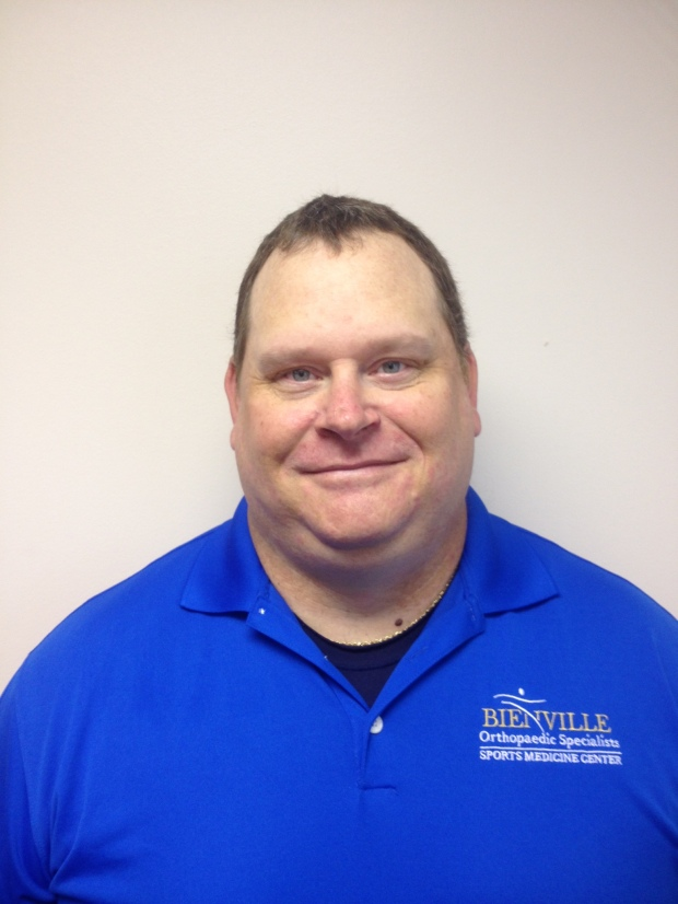 Male Athletic Trainer smiling in royal blue polo shirt