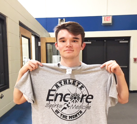 young man posing for photo and is holding up a t-shirt that read Encore Sports Medicine Athlete of the Month