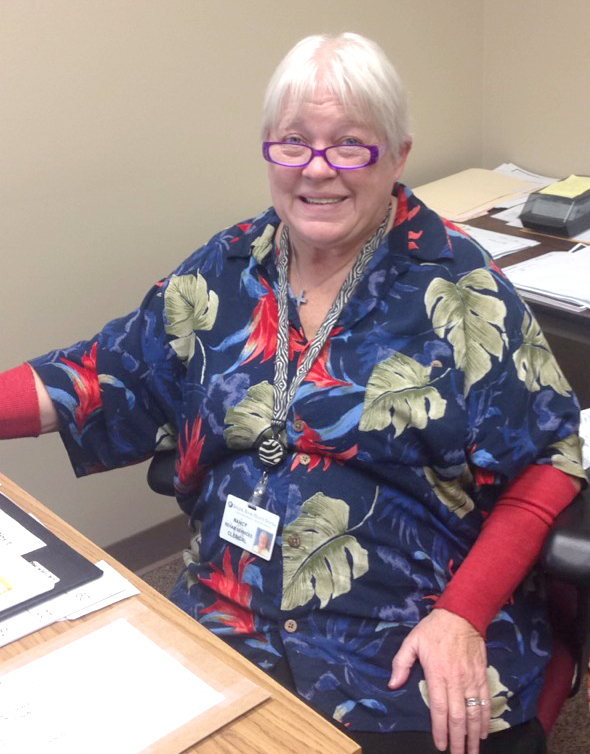 Lady in flowered shirt and glasses smiling while sitting at a desk in an office