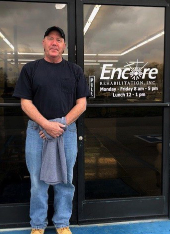 man smiling, posing in front of the glass doors to Encore Rehabilitation-Russellville clinic