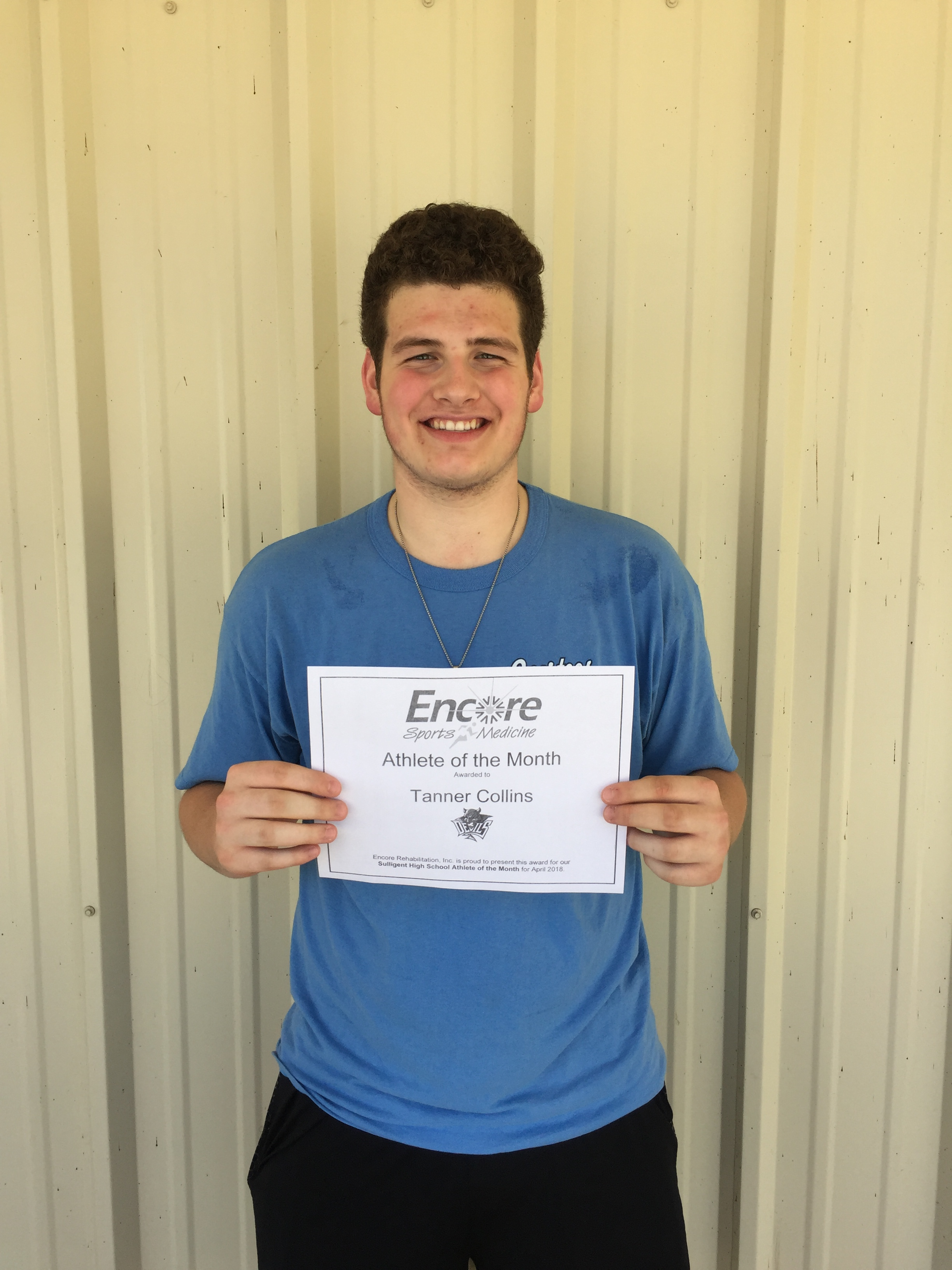 Young man posing for photo with Encore Sports Medicine Athlete of the Month certificate