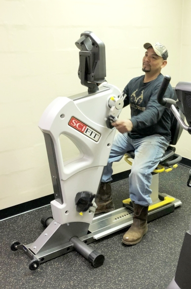 Man sitting on an exercise machine strengthening his shoulders
