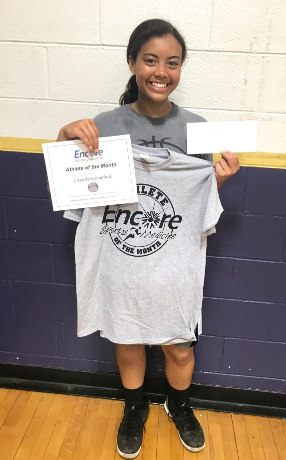 Young female athlete leading smiling and holding a t-shirt that read Encore Sports Medicine Athlete of the Month