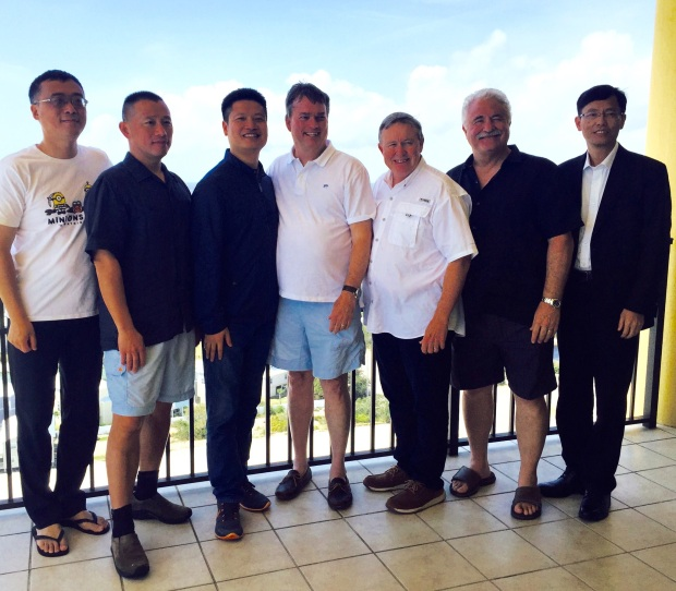 Several men posing for photo while standing on the balcony overlooking beach in southern Alabama