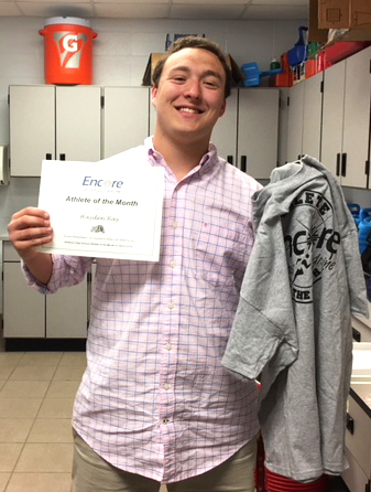 Young man smiling and posing for photo holding a paper certificate and t-shirt which read Encore Sports Medicine Athlete of the Month