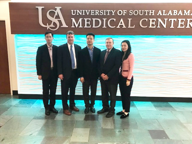 business professionals posing in front of glass wall which reads University of South Alabama Medical Center
