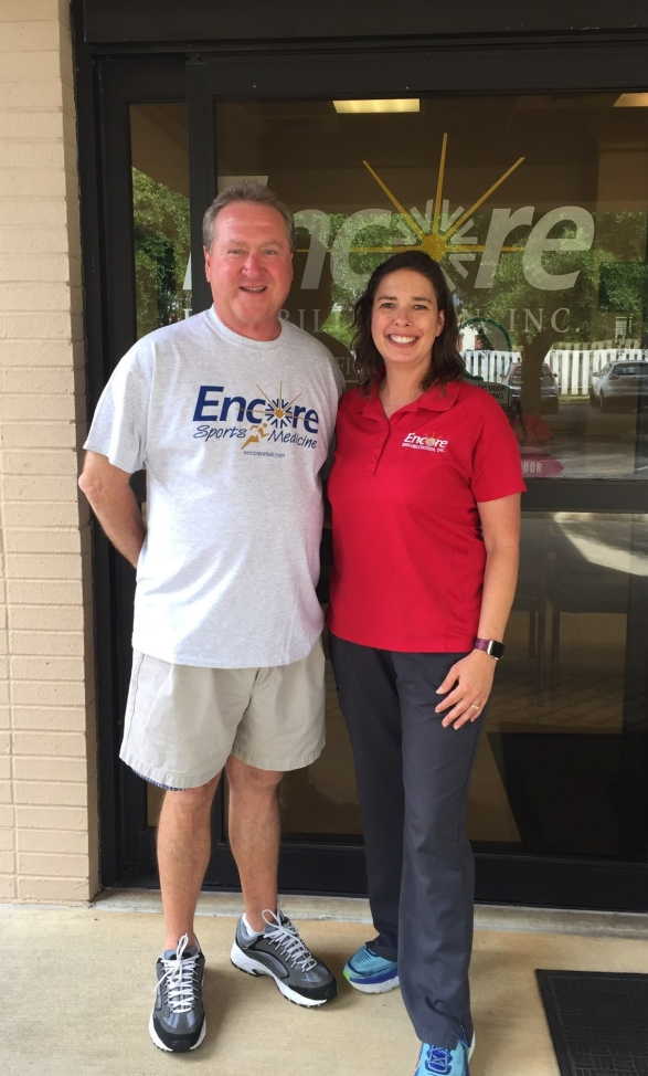 Two people smiling and posing in front of Encore Rehabilitation-Enterprise, Alabama.