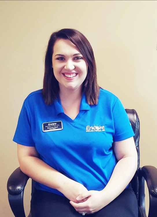 Brianna Deal, Front Desk Coordinator, for Encore Rehabilitation-Eufaula seated in a chair, smiling for photo