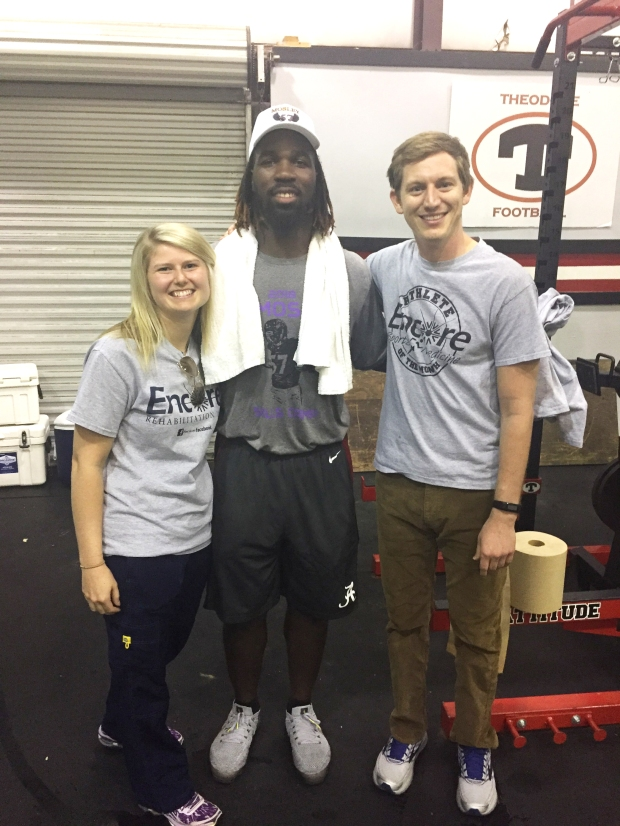 NFL Linebacker CJ Mosley posing for photo at Theodore High School (Alabama) with Encore Rehabilitation Therapists Jessie Bowles, LPTA, and Clinician Director Jack Dockery, PT