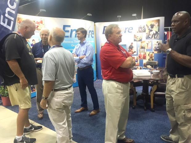 Coach Doug Barfield along with Encore Rehabilitation President Paul Henderson with Gary Barfield and Jonathan Henderson visiting with guests in the Encore Rehabilitation Booth at the AHSAA Summer Conference Expo.