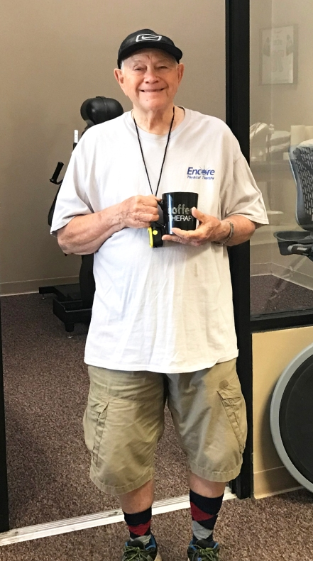 Man smiling, standing with coffee cup in hand. Man is Gordon Coats, Patient of the Month for Encore Rehabilitation-Tuscaloosa.