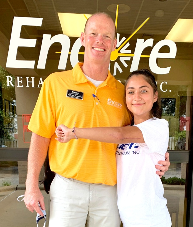 Patient of the Month Allisa Flores shows her scar from her broken elbow while she poses with #EncoreRehab Enterprise Clinic Director Randy Riley, PT